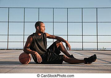 African sportsman resting at the playground with basketball...