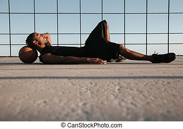 Afro american sports man lying on the playground with...
