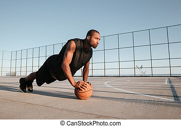 Sports man doing plank exercise with ball at the playground...