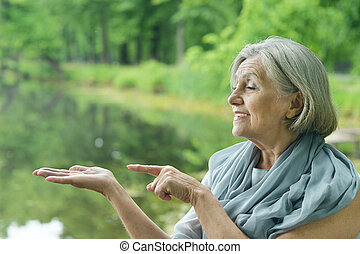 elderly woman shows on hand on nature