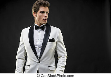 Luxury, elegant man in a white suit tuxedo with bow tie...
