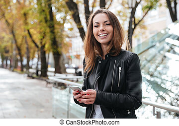 Cheerful woman standing and using smartphone in the city -...