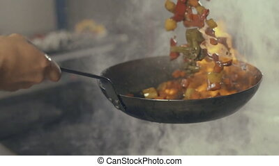 Chef in a restaurant kitchen making flambe with vegetables...