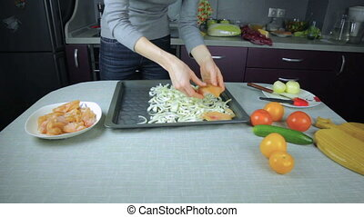 Chef arranges raw chicken on a baking sheet - Girl chef...