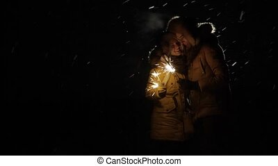 Young beautiful couple and burning sparklers in night with...