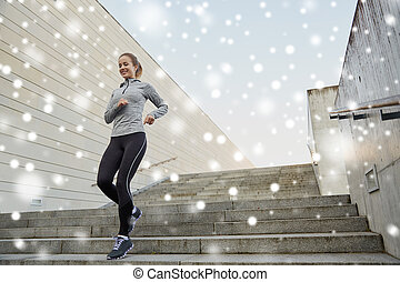 happy sporty woman running downstairs in city - fitness,...