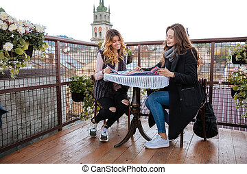 Models in cafe. good landscape. girls in coats