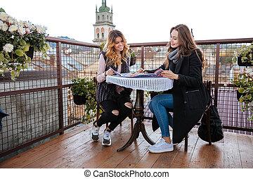 Models in cafe. good landscape. girls in coats