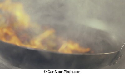 Chef in a kitchen cooking flambe style close-up. - Chef...