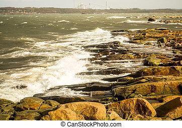 waves crashing at shore in swedish landscape - rock at the...