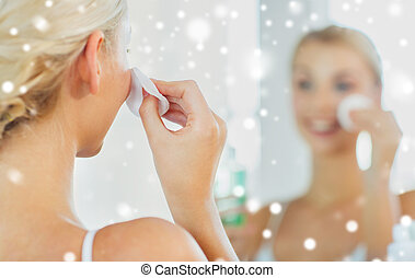 close up of woman cleaning face at bathroom - beauty, skin...