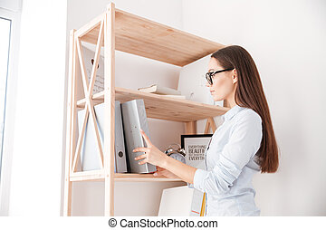 Businesswoman taking folder from book shelf - Young casual...
