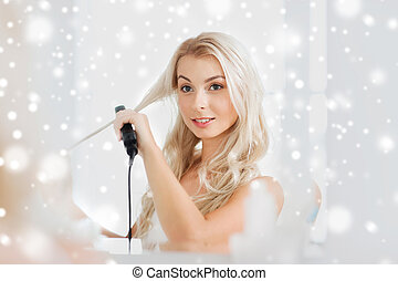 woman with styling iron doing her hair at bathroom - beauty,...
