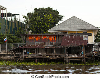 The old shacks, hovel houses stand on stilts in the water on...