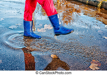 girl standing in a puddle of water splashes - girl in blue...