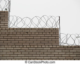 brick fence with barbed wire