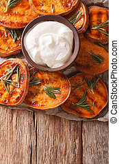 roasted sweet potato with sour cream closeup. vertical top...