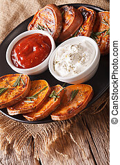 Grilled sweet potatoes with sour cream and ketchup closeup....