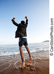Free Business Man - A business man jumping on the beach,...