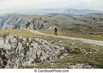 athlete cyclist on mountainbike rides on a mountain trail...