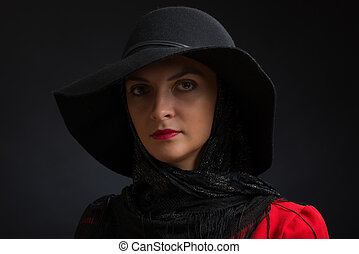 The young beautiful woman in a black hat with wide fields,...