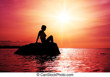Pink sunset woman - Silhouette of a beautiful woman sitting...