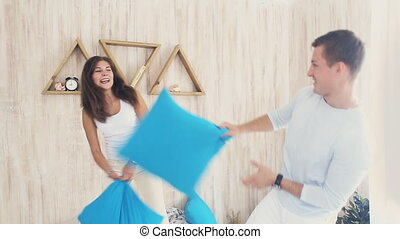 young loving couple pillow fight