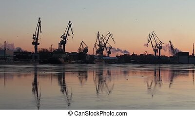 Silhouettes of of portal cranes on the horizon - St....