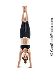 Young sporty woman doing headstand yoga asana pose isolated...