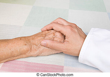 doctor and elderly patient - hand of a doctor holding the...