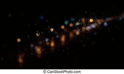 Raindrops running down on window glass - Traffic Rain Bokeh...