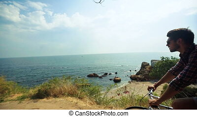 Young active muscular man looking at the sea and riding his bicycle on the stony beach.