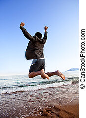 Success Business - A happy business man jumping by the ocean...