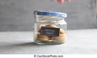 writing MUTUAL FUNDS, and money in jar - writing MUTUAL...