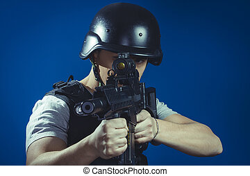 Security, paintball sport player wearing protective helmet aiming pistol ,black armor and machine gun