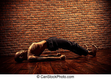 experienced trainer - Mature man practicing yoga. Brick wall...