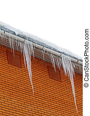 Snow-covered roof with icicles on white background -...