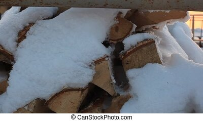 snowy birch firewood lie during sunset on the banks of the...