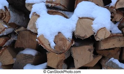 snowy birch firewood lie during sunset on the banks of the river Ob Novosibirsk