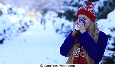 Smiling young woman drinking coffee in cold winter - Smiling...