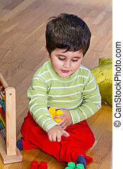 Toy, Funny little boy playing with plastic colorful blocks, studio shot