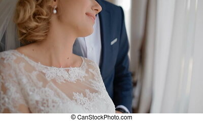 Happy bride and groom stand near the window. Young caucasian...