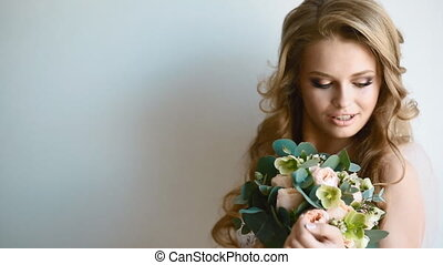 Beautiful bride posing near the window holding bouquet....