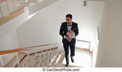 Groom walk upstairs with bouquet