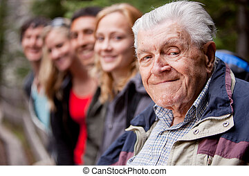 Elderly Man - An elderly man in front of a group of young...