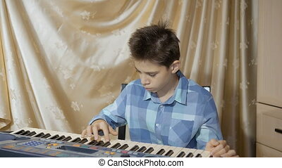 Happy boy teenager playing on an electronic piano, composes...