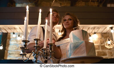 Bride and groom cut wedding cake in loft bar. They hold the...