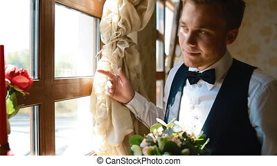 Groom look at the window holding wedding bouquet in his...