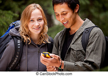 GPS Camping Friends - A man and woman looking at a gps in...