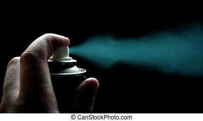 Spray can Sprays Cyan Paint - Hand with spray can sprays...